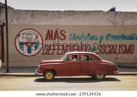 Havana, CUBA - JANUARY 20, 2013: Old classic American car drive on street of Havana,CUBA on front of political slogan on wall. Old American cars are iconic sight of Cuba street. - stock photo