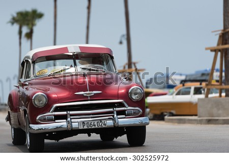 HAVANA, CUBA - JULY 05, 2015: HDR red american classic car drive on the street at the Malecon.