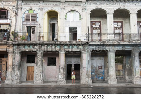 HAVANA, CUBA - JUNE 2011: Cuban woman holding a baby looks out onto a rainy street from covered walkway of dilapidated row of colonial buildings