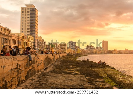 HAVANA,CUBA - MARCH 5, 2015 : Cubans sitting on the Malecon seawall during a beautiful sunset - stock photo
