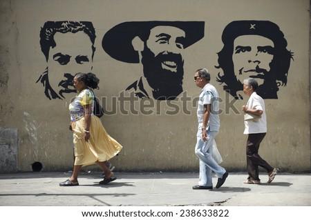 HAVANA, CUBA - MAY 16, 2011: Cuban people walk in front of stencil billboard featuring Julio Antonio Mella, Camilo Cienfuegos, and Che Guevara, three leaders of the Communist Revolution. - stock photo