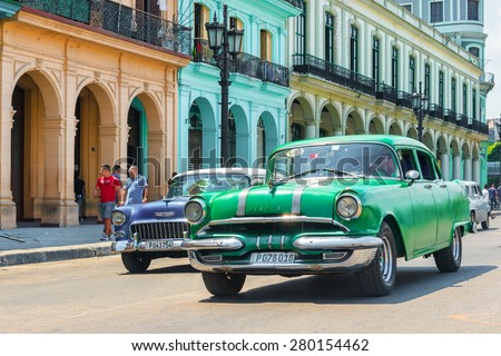 HAVANA,CUBA - MAY 20,2015 :  Vintage american cars next to colorful traditional buildings in Old Havana - stock photo