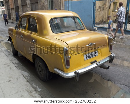 HAVANA, CUBA - NOVEMBER 20:  A  vintage yellow car parked along a sidewalk in the center of the town ,on november 20, 2014, in Havana, Cuba  - stock photo