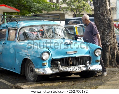 HAVANA, CUBA - NOVEMBER 20: An old man washes an american vintage blue car in the center of the town ,on november 20, 2014, in Havana, Cuba  - stock photo
