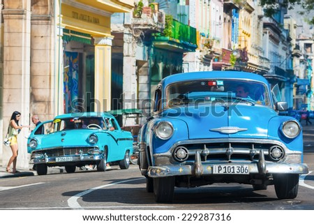 HAVANA,CUBA - NOVEMBER 6, 2014 : Old classic cars used a taxis circulating on a well known street in Havana - stock photo