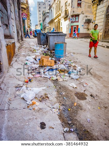 HAVANA, CUBA - OCT 28 - Man walks by piles of trash and garbage in the streets of Havana, Cuba on Oct 28, 2015 - stock photo