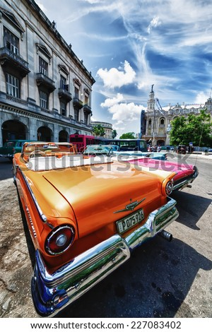 HAVANA, CUBA - OCTOBER 8, 2014: Old classic American cars in street city Havana. Before a new law issued on October 2011, Cubans could only trade cars that were on the road before 1959. Wide angle. - stock photo