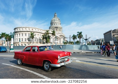 HAVANA, CUBA - OCTOBER 8, 2014: Old classic American red car rides in front of the Capitol. Before a new law issued on October 2011, Cubans could only trade cars that were on the road before 1959.  - stock photo