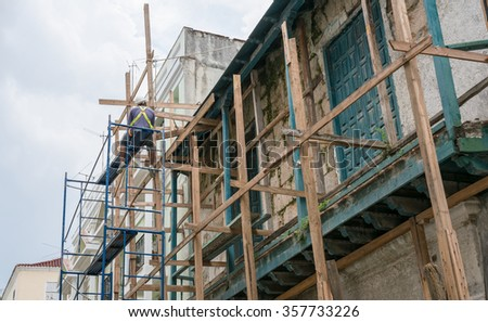Havana, Cuba - 7 September 2015: Cuban worker man sitting on scaffolding at construction site in Havana, Cuba.