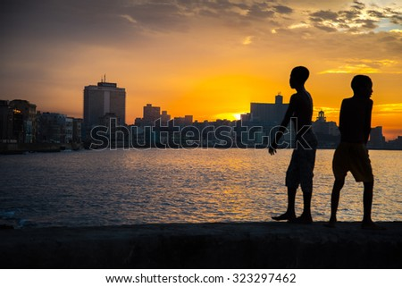 Havana, Cuba - September 25, 2015: Group of young kids play and jump to Atlantic from famous promenade wall Malecon in Havana, Cuba. Scene captured just before sunset at Malecon in Havana, Cuba. - stock photo