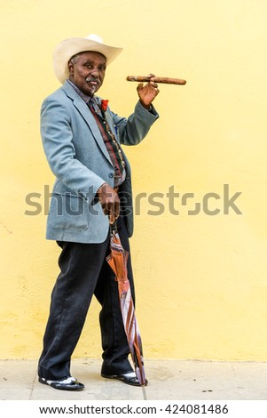 Havana, Cuba - September 27, 2015: Traditional Cuban man smoking big cuban cigar on yellow wall background in Havana, Cuba