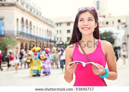Havana, cuba - tourist with travel guide book on Plaza de Armas, Havana, Cuba. Young woman traveler smiling happy. - stock photo