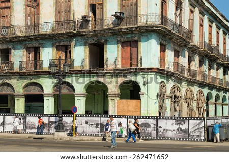HAVANA - FEB 13: Old building surrounded with a film-like fence with balconies and pedestrians on the street in Old Town of Havana on February 13, 2015. - stock photo