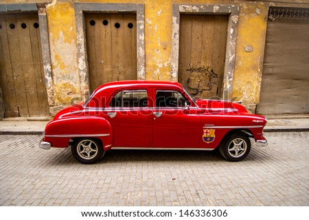HAVANA - FEBRUARY 12: Classic car parked in front of old building on February 12, 2013 in Havana. These old cars are usually in good condition as they are renovated very often. - stock photo