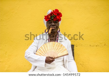 HAVANA - FEBRUARY 2: Old lady with a cigar dressed in typical cuban clothes February 2, 2013. Iconic characters like this are an attraction for the over 2 million tourists who go to Cuba each year. - stock photo