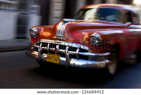 HAVANA - JANUARY 15: A classic Chevrolet car driving in a street on January 15, 2013 in Havana. These old and classic cars are an iconic sight of the island - stock photo