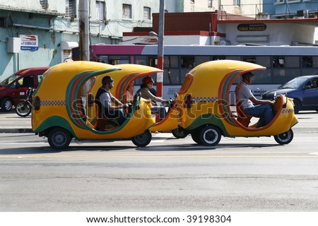 HAVANA - MARCH 16: Cuban coco taxis on the street March 16, 2009 in Havana. The famous tiny taxi cabs are everywhere on the streets and can fit in maximum 2 passengers. - stock photo