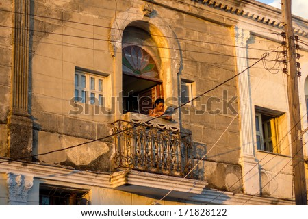 HAVANA-SEPTEMBER 10:Cuban girl on a typical balcony September 10,2013 in Havana.With over 2 million inhabitants,Havana is the capital of Cuba and the largest city of the Caribbean - stock photo
