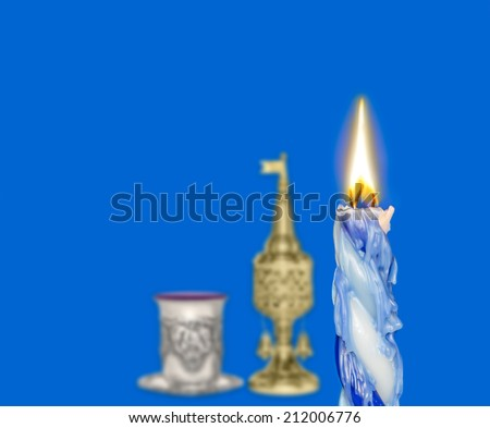 Havdalah set, focus on braided lit candle dripping wax. Jewish religious ritual objects for conclusion of Sabbath. Kiddush cup, red wine, metal spice container tower shape with bell and flag.  - stock photo