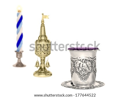 Havdalah set, selective focus on silver kiddush wine cup. Jewish religious ritual after conclusion of Sabbath. Braided lit candle. Gold color spice container, traditional tower shape with bell, flag.  - stock photo