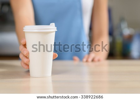 Have a break. Selective focus of  cup of coffee in standing on the table with waitress standing in the background and holding it - stock photo