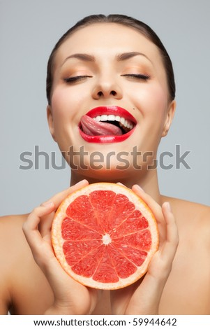 Have a lick. Pretty woman with delicious grapefruit in her arms. - stock photo