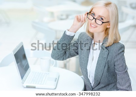 Have a rest. Pleasant smiling attractive business woman holding her glasses and sitting at the table while resting in the cafe