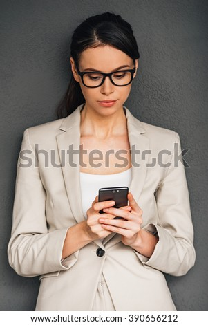 Have some work to do. Beautiful young businesswoman using her smart phone while standing against grey background - stock photo