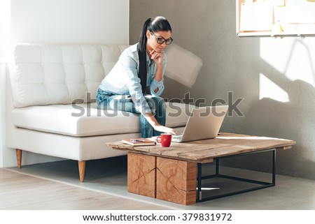 Have some work to do. Beautiful young woman in glasses working on laptop while sitting on the couch in office - stock photo
