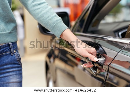 Have to try this one. Cropped closeup of a woman opening car door at the car salon - stock photo