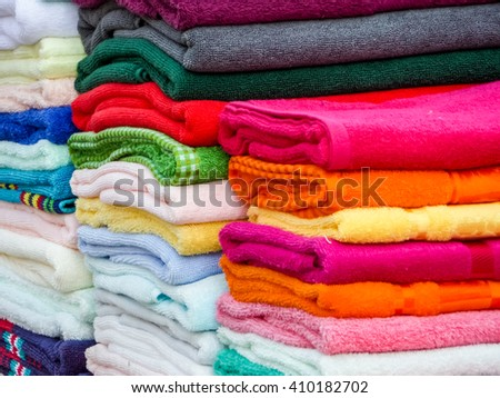 have towels in lots of sizes, styles and colors and towel is a piece of absorbent fabric or paper used for drying or wiping the body or a surface - stock photo