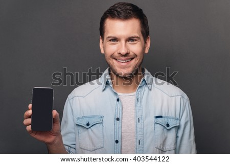 Have you seen this? Cheerful young man shoving his smart phone with copy space and looking at camera with smile while standing against grey background - stock photo