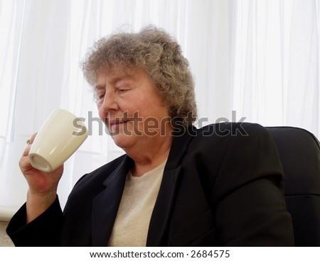 Having a coffee break older female worker - stock photo
