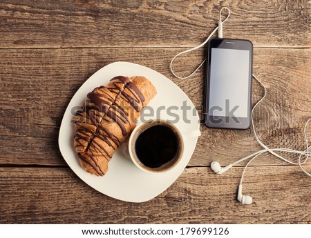 Having coffee and croissants with smartphone and headphones - stock photo