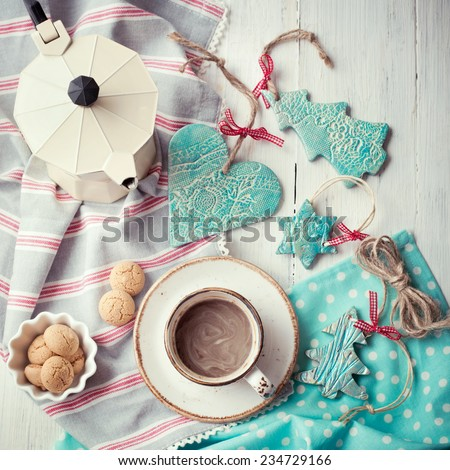 Having coffee at Christmas morning: cup of espresso set with handmade ceramic decorations and italian coffeemaker. Toned photo. - stock photo