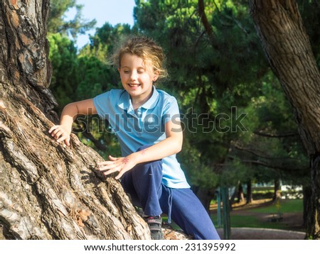 Having fun climbing on a tree in a park on sunny fall day. - stock photo