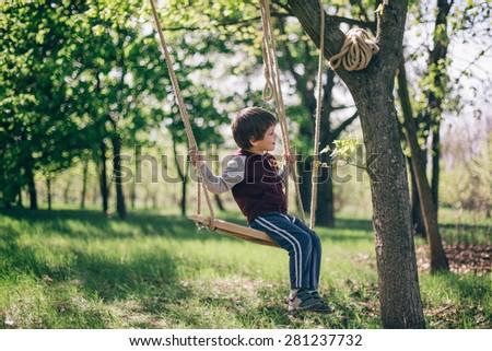 Having fun. Little cute boy swinging in woods on hand made swing - stock photo