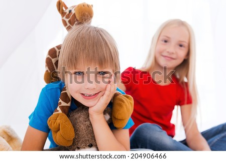 Having fun together. Two cute children having fun while sitting together on bed