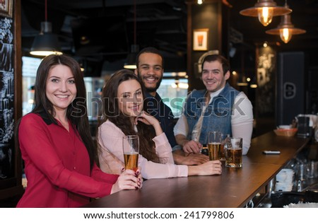 Having fun with beer and friends. Portrait of young beautiful girl is standing in a pub with glass of beer and smiling. Her friends are standing next to her and drinking beer - stock photo