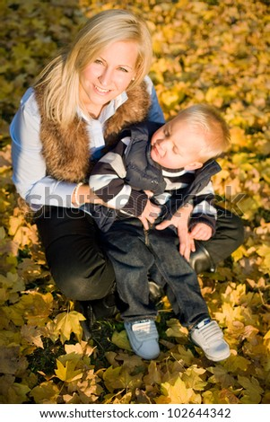 Having fun with mom, beautiful young mtoher with her son outdoors in the park at fall. - stock photo