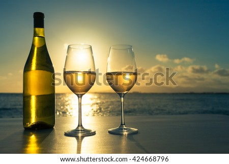Having glass of wine on the beach at sunset - stock photo
