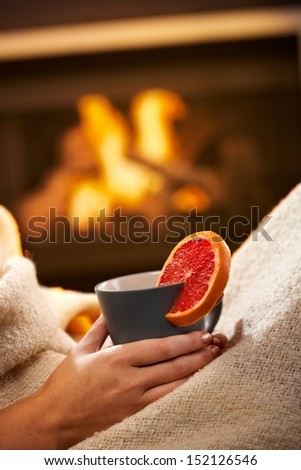 Having hot tea with blood orange in front of fireplace, female hand holding mug. - stock photo