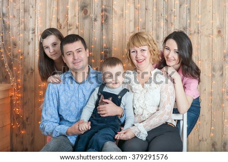 Having many children family sit near wood wall with a garland - stock photo