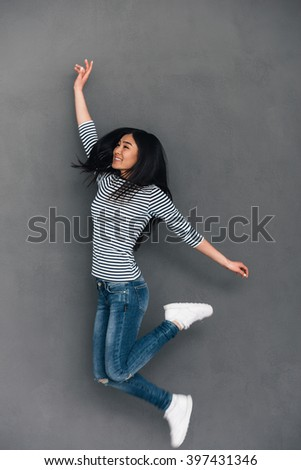 Having so much fun! Beautiful young cheerful Asian woman looking away with smile while jumping against grey background - stock photo