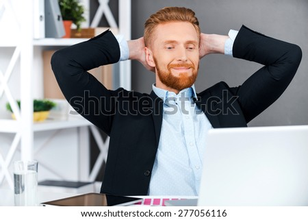 Having some rest for productive work. Cheerful bearded businessman holding head in hands while sitting at his working place - stock photo