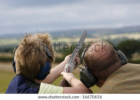 Having tuition the young boy aims the gun - stock photo