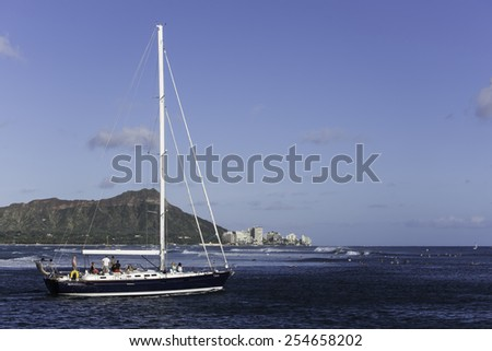 Hawaii-August 5, 2014:  Sailboat with Diamond Head and surfers in the background, enjoy swells and winds generated by Category 1 Hurricane Iselle, 300 miles off shore. - stock photo