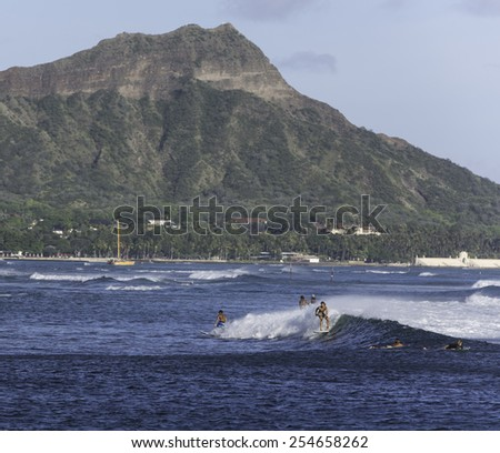 Hawaii-August 5, 2014:  Surfers with Diamond Head s in the background, enjoy swells and winds generated by Category 1 Hurricane Iselle, 300 miles off shore. - stock photo