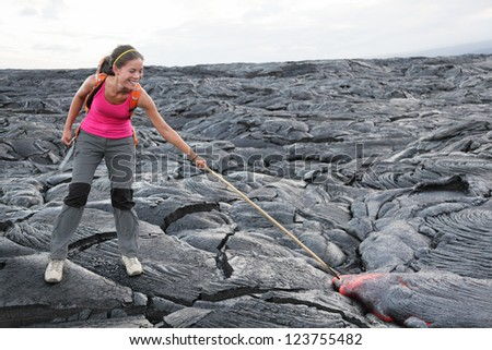 Hawaii Big Island lava tourist on volcano poking stick in red hot moving lava. flowing lava from Kilauea volcano around Hawaii volcanoes national park, USA. Young asian woman hiker. - stock photo