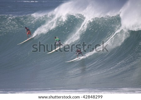 HAWAII - DECEMBER 8: Surfers take the drop in the Quicksilver Eddie Aikau Big Wave Invitational  on December 8, 2009 at Waimea Bay, Hawaii. Waves for this event must be 20 feet or bigger. - stock photo